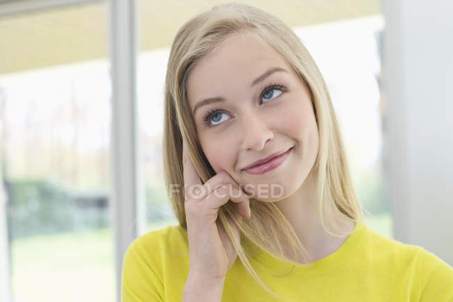 Close-up of blond woman smiling and looking away in front of window — Stock Photo