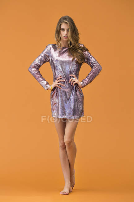 Portrait of young stylish female model posing in glossy dress on orange background — Stock Photo