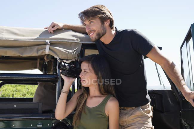 Женщина с парнем снимает с видеокамерой перед открытым фургоном — стоковое фото