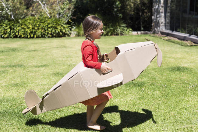 Little girl playing with cardboard airplane on lawn — Stock Photo