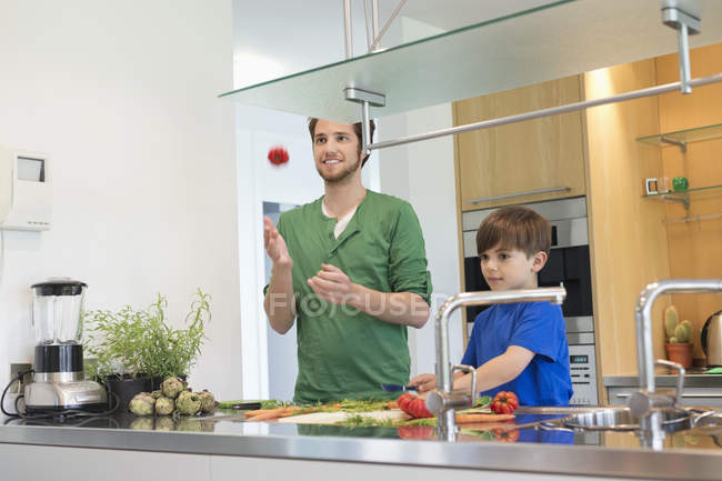Man and son cutting vegetables in modern kitchen — Stock Photo