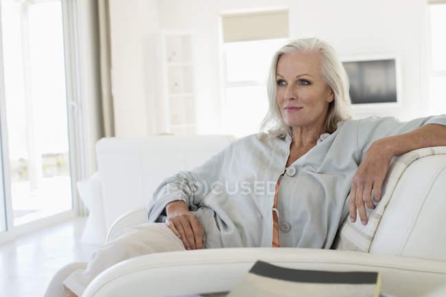 Entspannte Frau sitzt auf Couch und denkt nach — Stockfoto