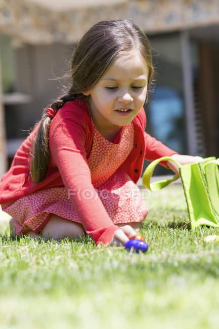 Дівчина, підбираючи великодні яйця на зеленій галявині — стокове фото