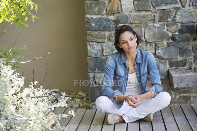 Женщина, сидящая на паркете и мечтающая — стоковое фото