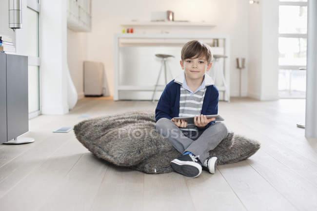 Портрет улыбающегося мальчика с цифровым планшетом в современной квартире — стоковое фото