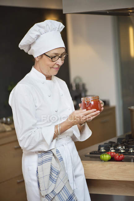 Portrait of woman in chef costume holding jar of tomato sauce — Stock Photo