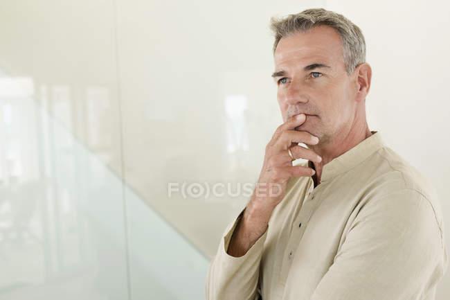 Продуманий зрілою людиною, що стоїть перед стіни — стокове фото