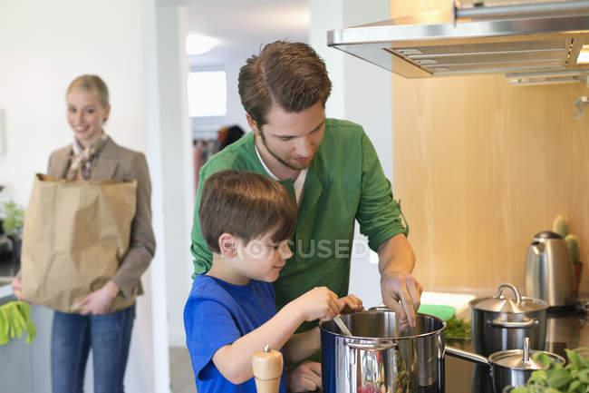Чоловік і син приготування їжі для матері після покупки — стокове фото