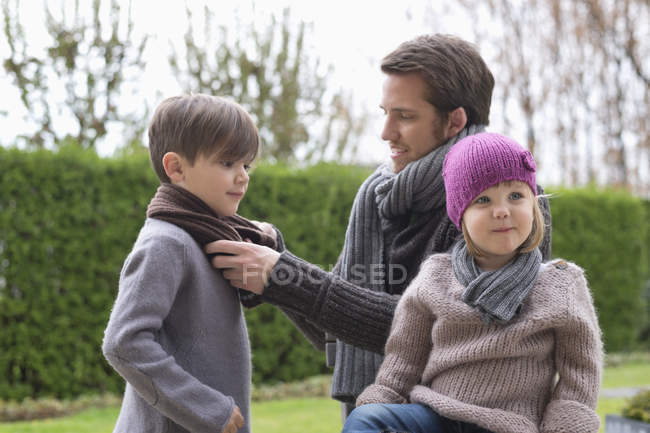 Man putting on warm clothing on children outdoors — Stock Photo
