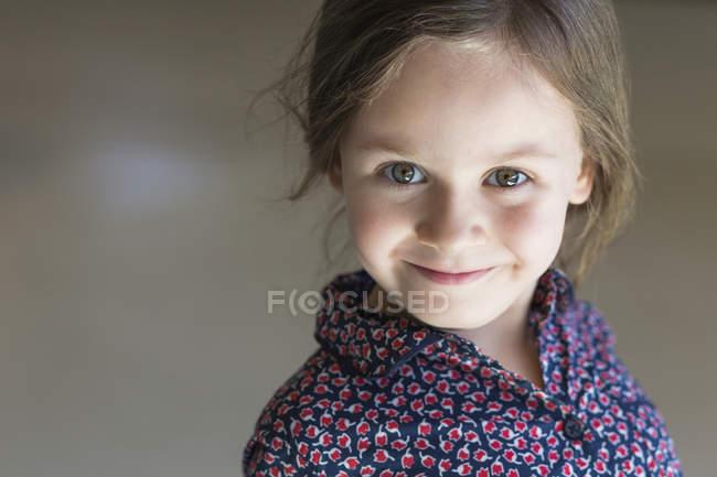 Портрет милою дівчинкою, посміхаючись в приміщенні — стокове фото