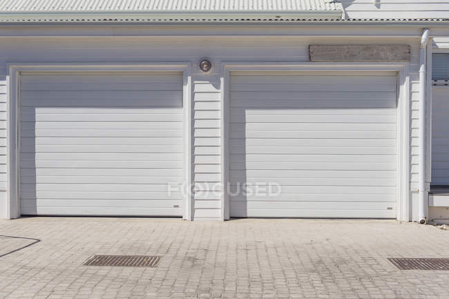 Closed shutters of white building in countryside — Stock Photo