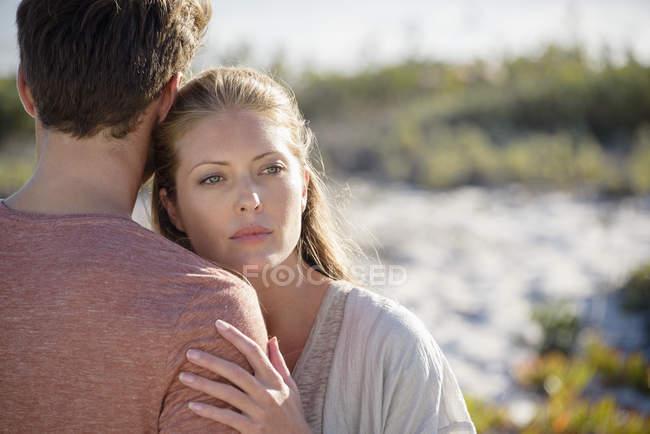 Coppia romantica che si abbraccia in piedi sulla costa — Foto stock