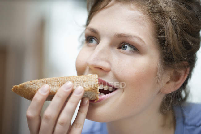 Portrait of young woman eating toast with cream spread — Stock Photo