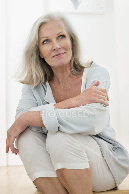 Dreamy senior woman sitting on floor at home and looking away — Stock Photo