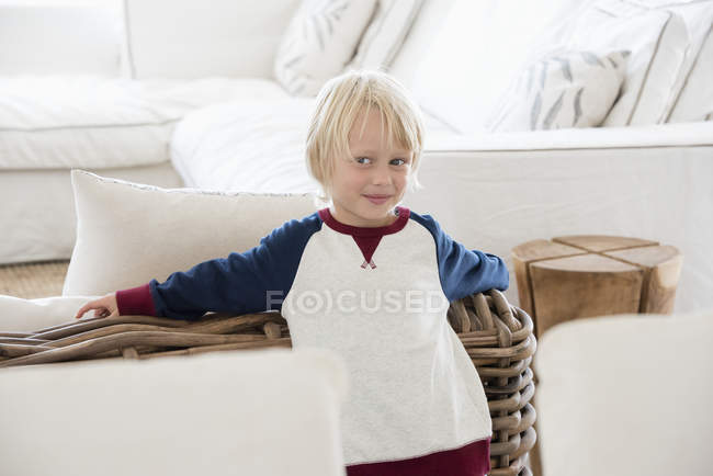 Portrait of happy little boy with blonde hair standing in living room — Stock Photo