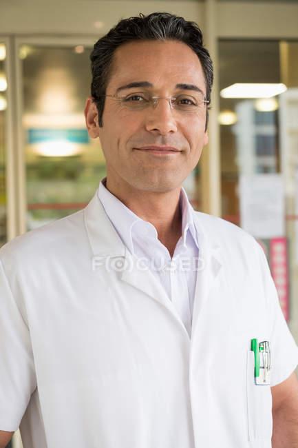 Retrato de un médico varón sonriendo en el hospital - foto de stock