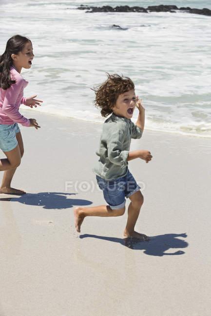 Crianças brincalhão correndo na praia de areia — Fotografia de Stock
