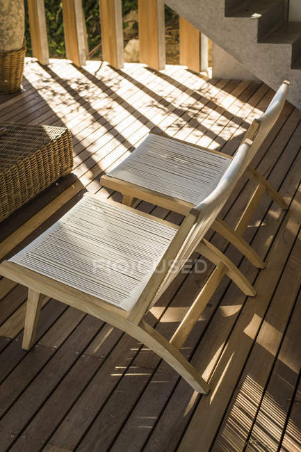 Zwei gestaltete Stühle auf Holzterrasse im Sonnenlicht — Stockfoto