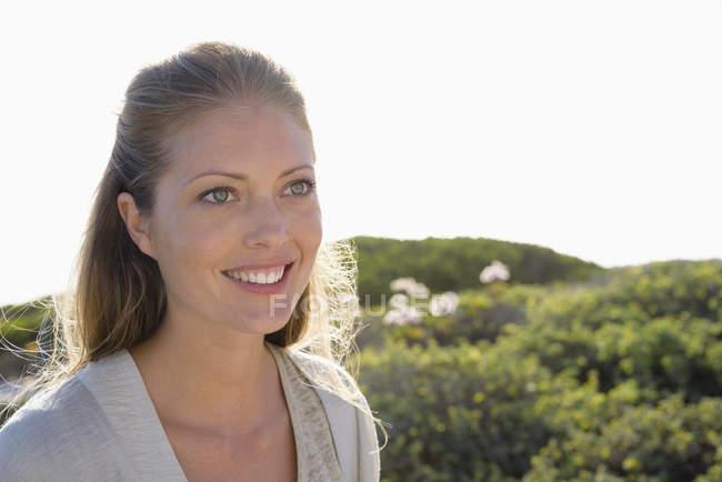 Nahaufnahme einer lächelnden Frau, die in der Natur wegschaut — Stockfoto