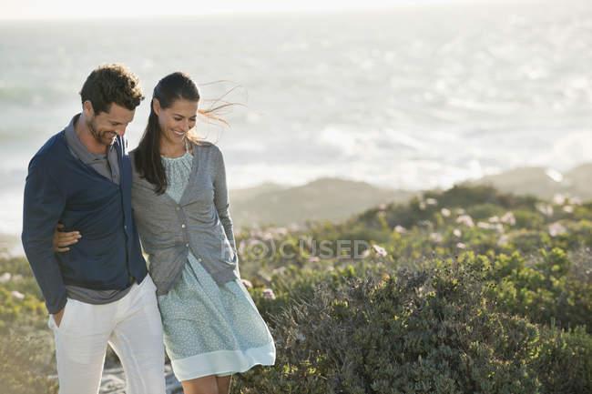 Smiling embracing couple walking on sea coast — Stock Photo
