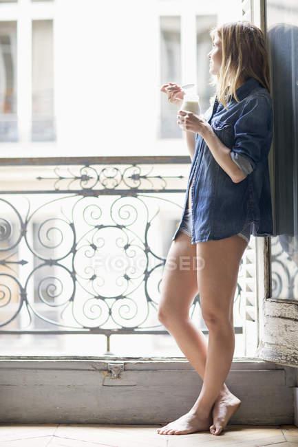 Mulher pensativa em camisa jeans em pé na varanda e beber leite — Fotografia de Stock