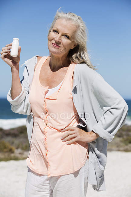 Portrait of woman holding bottle of probiotic drink on beach — Stockfoto