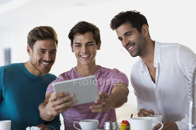 Close-up of three happy young men taking selfie with digital tablet — Stock Photo