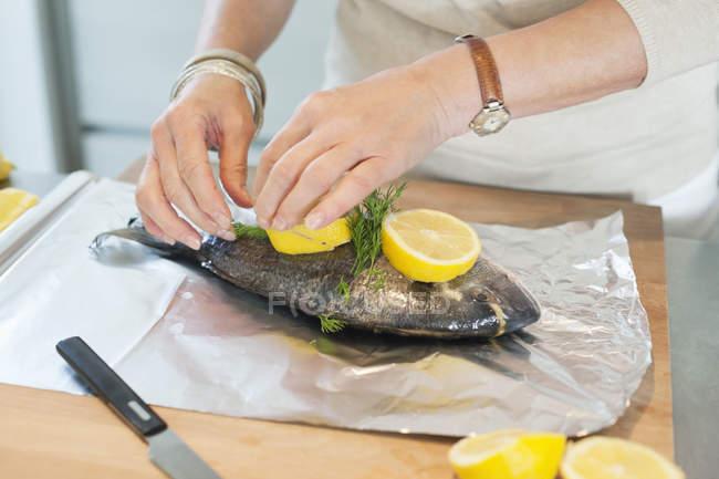 Nahaufnahme weiblicher Hände beim Zubereiten von Fisch in der Küche — Stockfoto