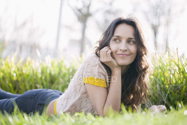 Sonriente mujer acostada en la hierba en el parque y mirando hacia otro lado - foto de stock