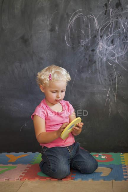 Mignonne petite fille jouant avec le puzzle de nombre devant un tableau noir — Photo de stock