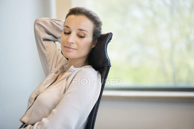 Elegant businesswoman day dreaming at desk in office — Stock Photo