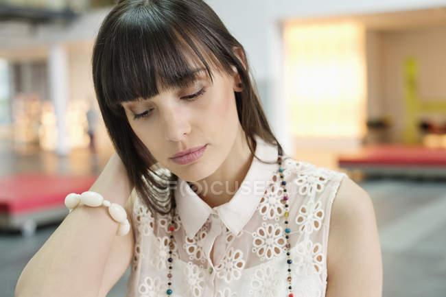 Primo piano di una giovane donna d'affari stanca che guarda in basso — Foto stock