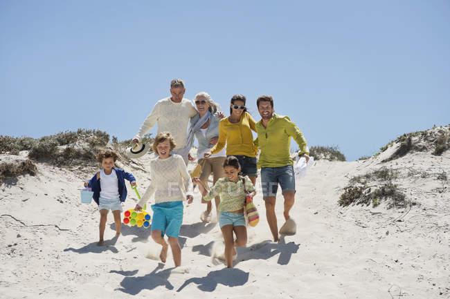 Счастливая семья гуляет по песчаному пляжу летом — стоковое фото