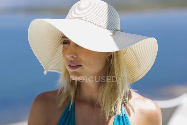 Primo piano della giovane bella donna che indossa il cappello da sole — Foto stock
