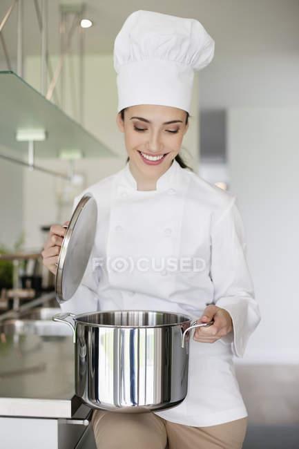 Щасливі жіночий шеф-кухар тримає каструлю кухні — стокове фото