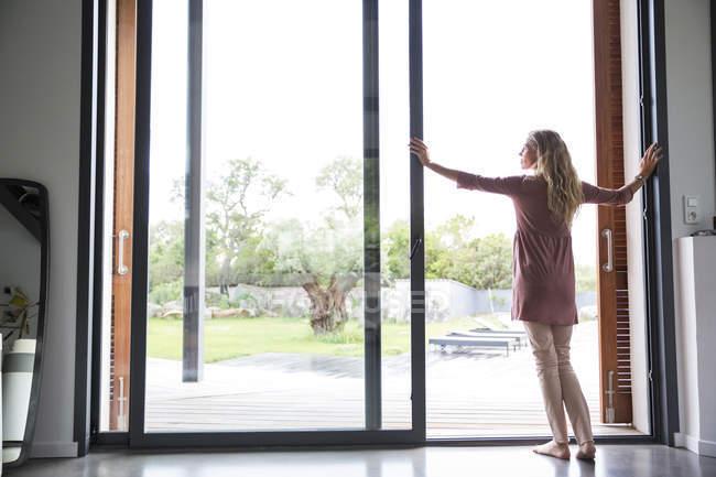 Женщина стоит у стеклянного окна с видом на сад — стоковое фото