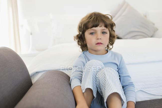Портрет грустного мальчика, сидящего на кровати — стоковое фото