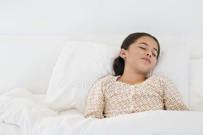 Kleines Mädchen schläft auf weißem Bett — Stockfoto
