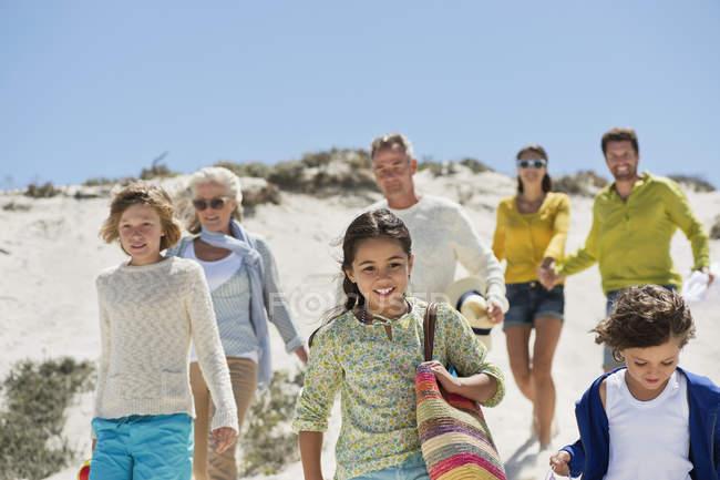 Glückliche Familie beim Wandern am Sandstrand im Sommer — Stockfoto