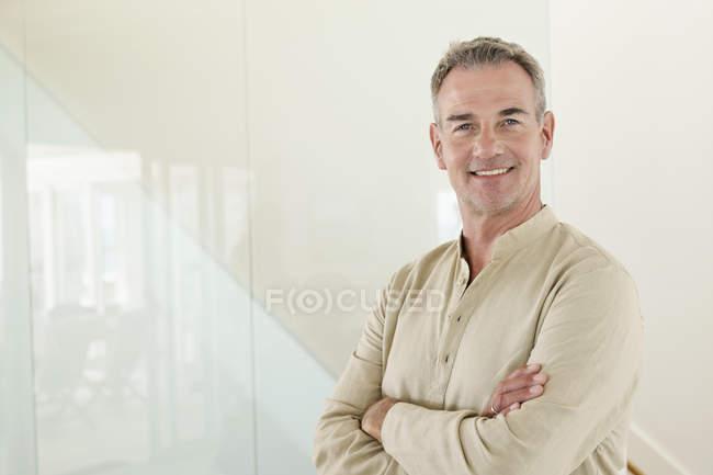 Ritratto di uomo maturo sorridente con le braccia incrociate in piedi davanti al muro — Foto stock