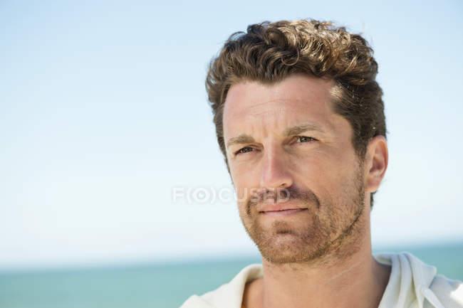 Close-up de homem pensativo na praia ensolarada — Fotografia de Stock
