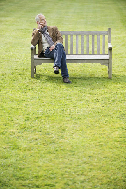 Elegant man sitting on bench in field and thinking — Stock Photo