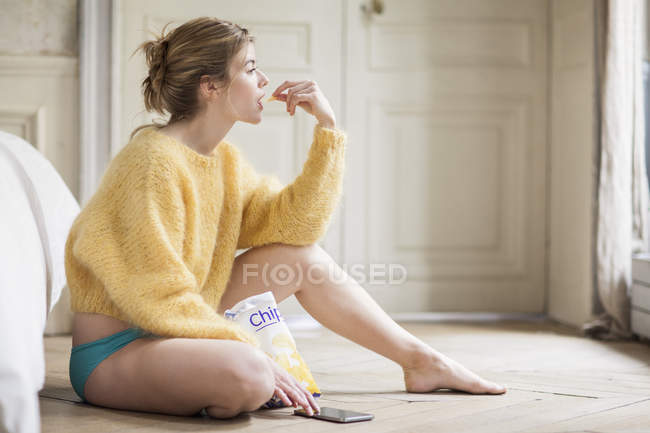 Woman sitting on floor at home with phone and eating chips — стоковое фото