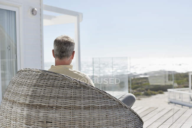 Man relaxing in wicker chair on terrace of house house on sea coast — Stockfoto