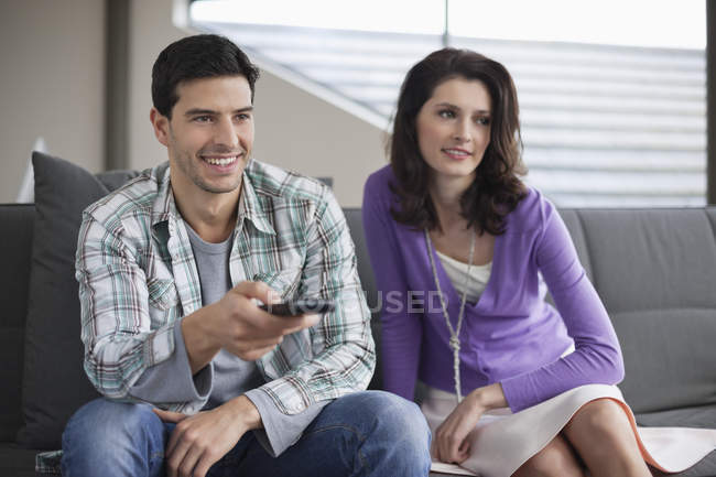 Couple watching television on couch at home — Stock Photo