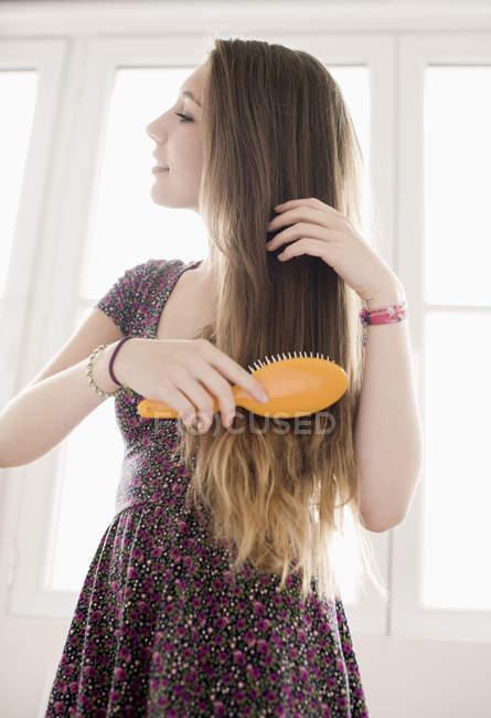 Teenage girl brushing hair in front of window — Stock Photo