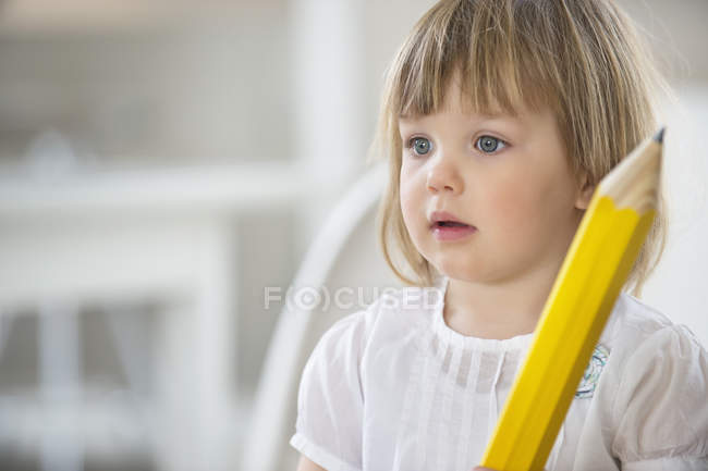 Милая маленькая девочка с большим карандашом — стоковое фото