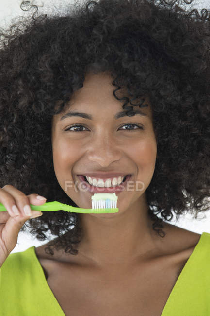 Portrait of woman with afro hairstyle brushing teeth - foto de stock