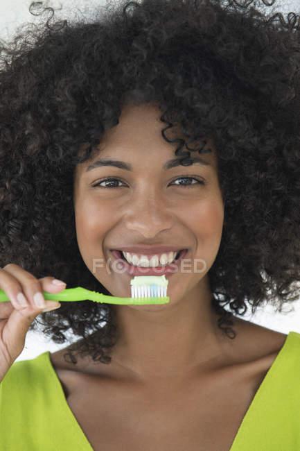 Retrato de mulher com penteado afro escovando dentes — Fotografia de Stock