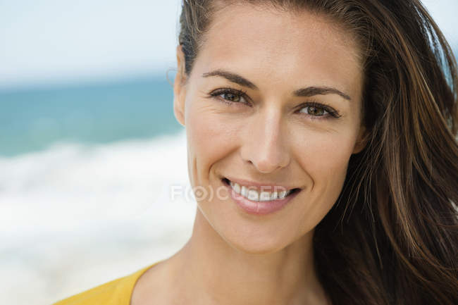 Portrait of woman with brown hair smiling on beach — Stock Photo